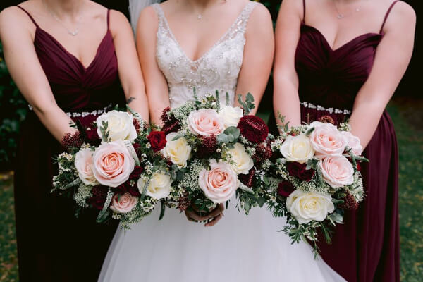 Bride and bridesmaids holding pink roses bouquets