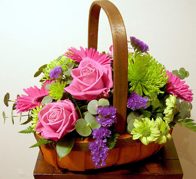 Basket of pink roses and green flowers