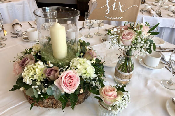 Pink and white floral display around wedding table