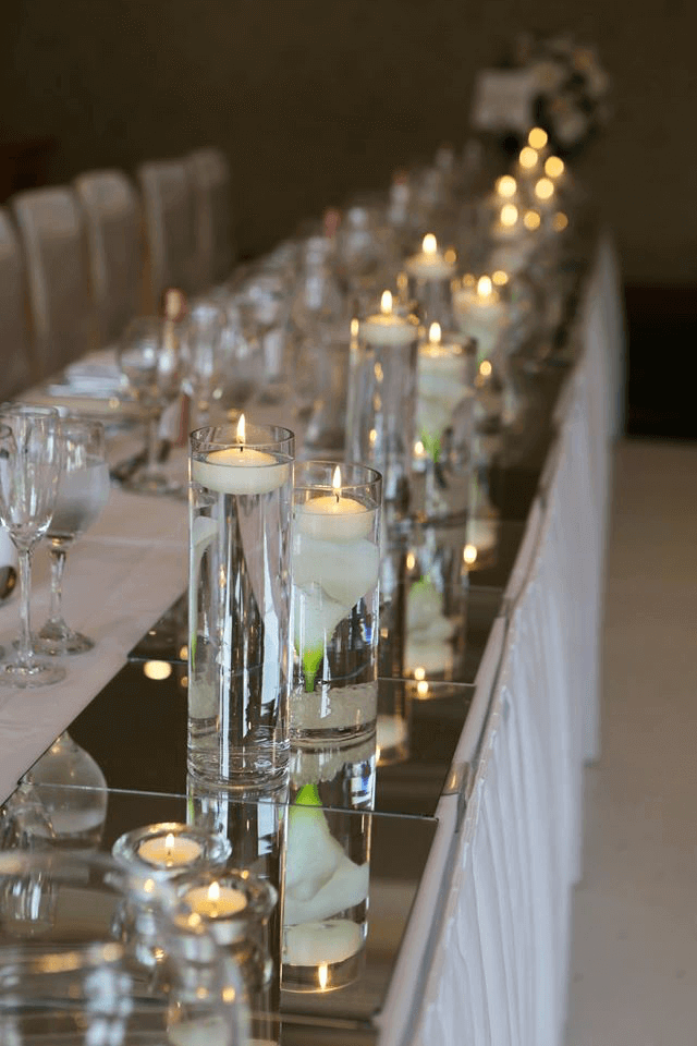 flutes filled with water and candles on top